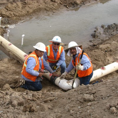 Crew members connect the piping that is used to join all of the dewatering points to the pump.